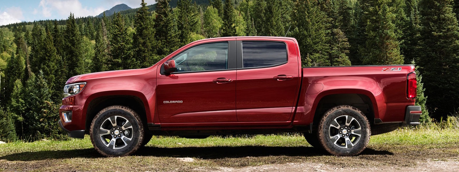 A red 2016 Chevy Colorado is shown from the side in front of pine trees while off-roading near Albany, NY.