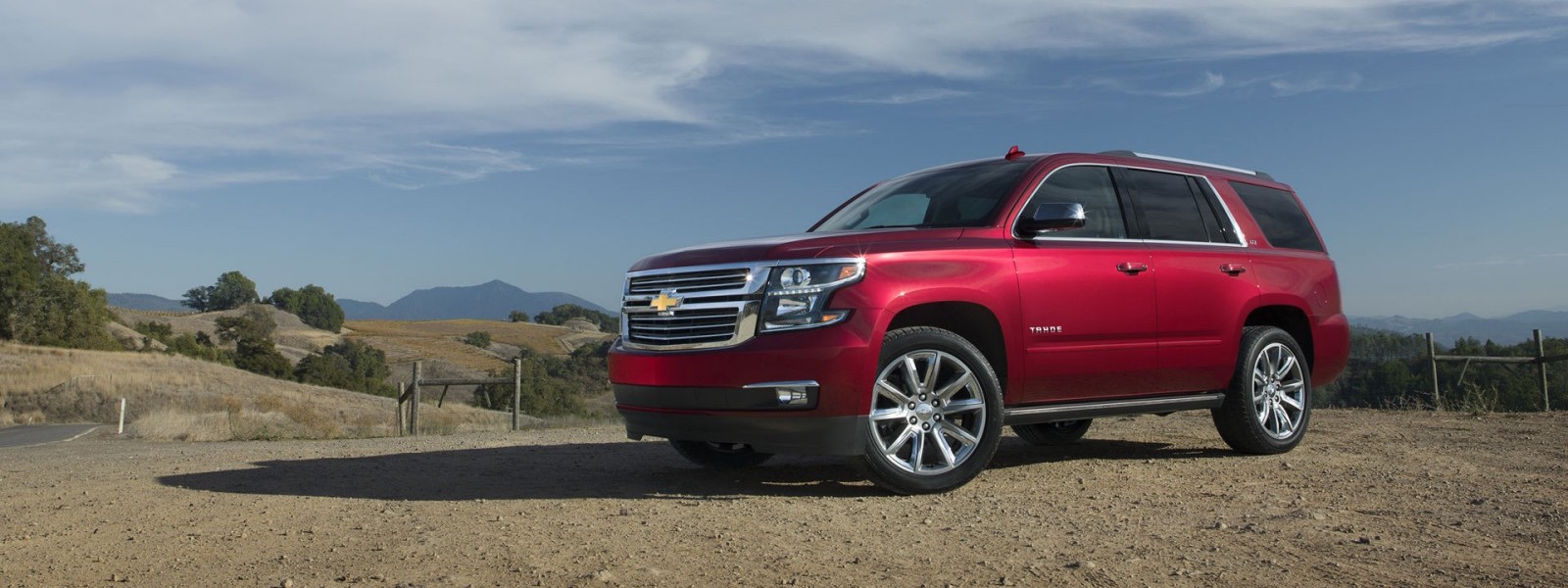 A red 2016 Chevy Tahoe is parked on a dirt pull of with distant mountains.