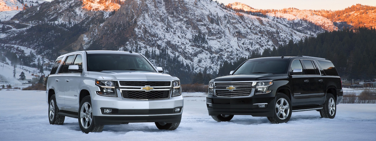 A silver and a black 2016 Chevy Tahoe are parked in front of snowy mountains outside of Albany, NY.