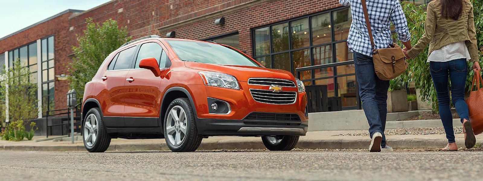 An orange 2016 Chevy Trax is parked in front of a brick building in Albany, NY.