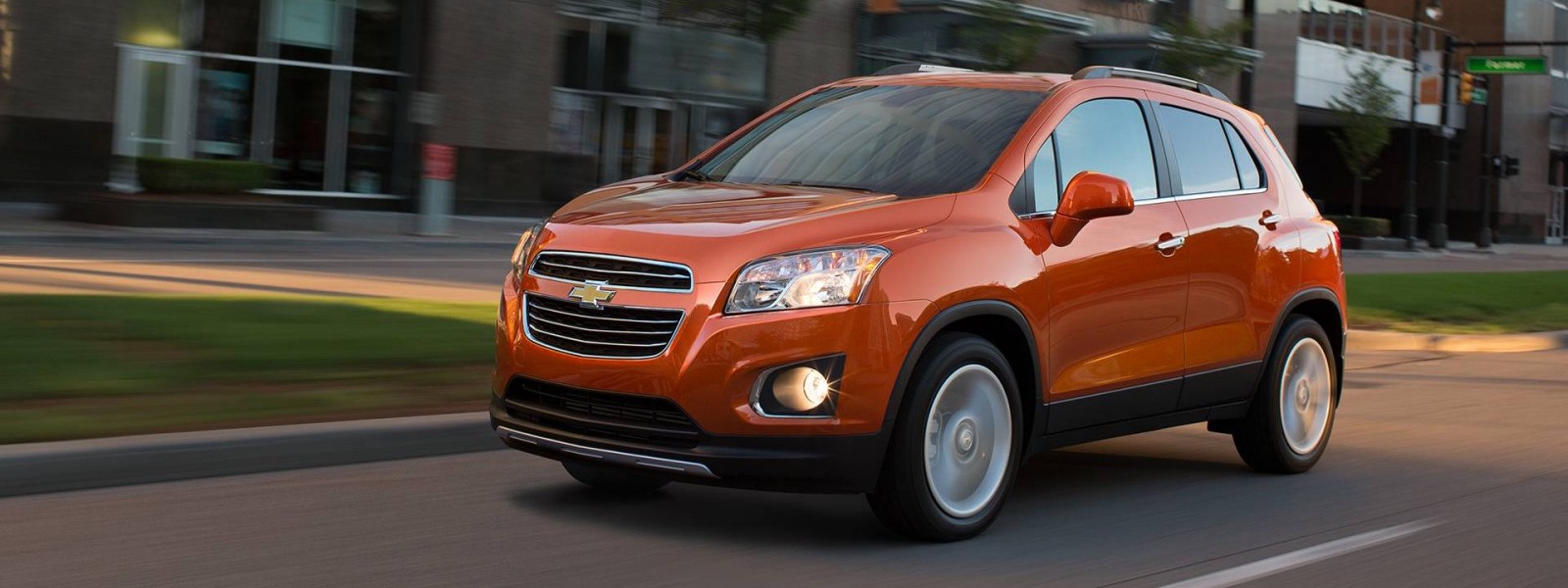 An orange 2016 Chevy Trax is driving down a blurred city street.