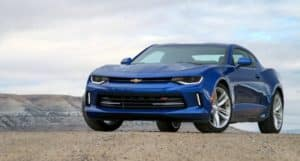 Blue 2015 Chevrolet Camaro sporty vehicle on a sandy ground with mountains in the background