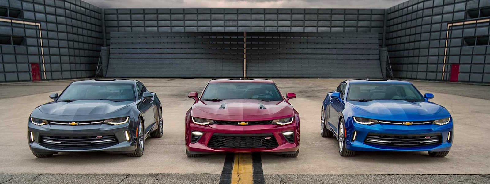 A grey, a red, and a blue 2016 Chevy Camaro are parked at a warehouse near Albany, NY.