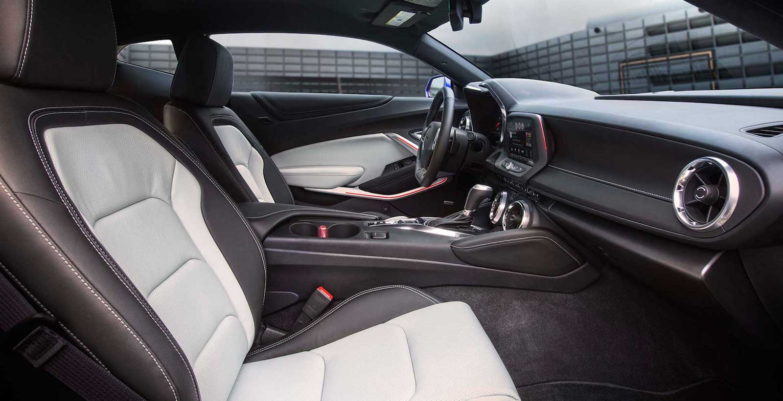 The black and white interior of a 2016 Chevy Camaro is shown from the side.