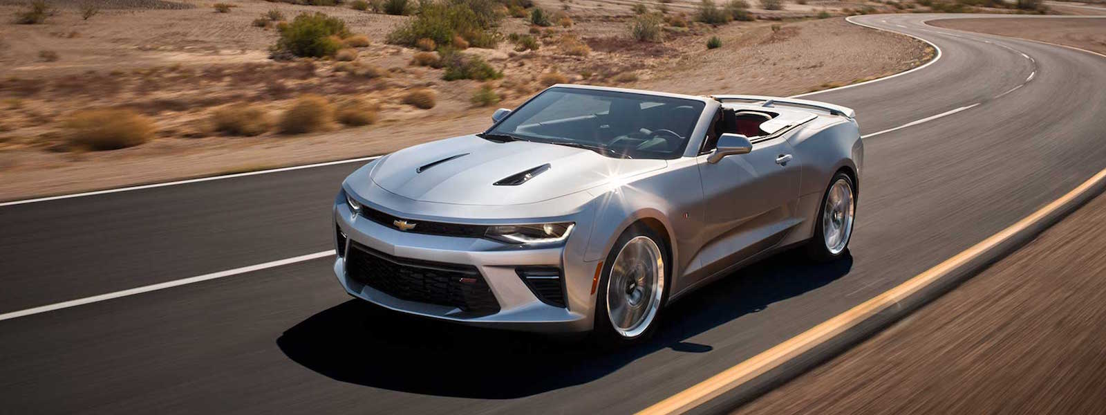 A silver 2016 Chevy Camaro is driving on a winding desert road.