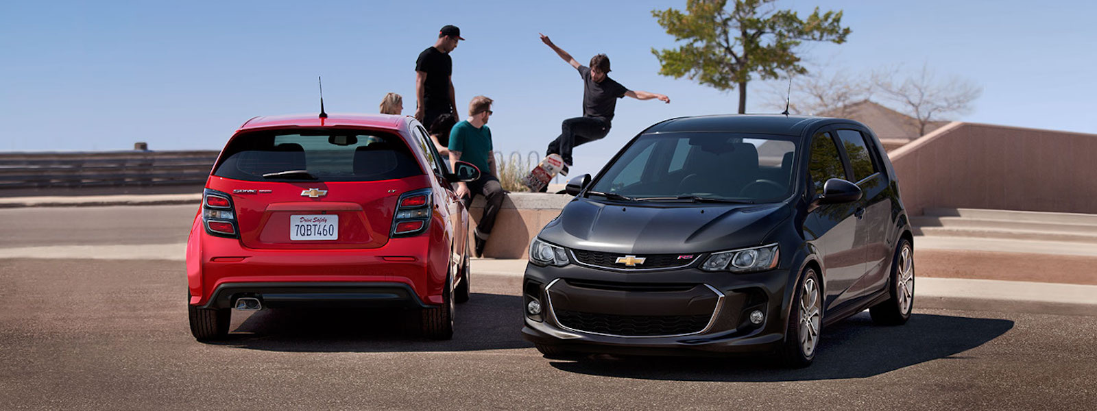 Teens are skateboarding next to a red and a gray 2017 Chevy Sonic at a park.