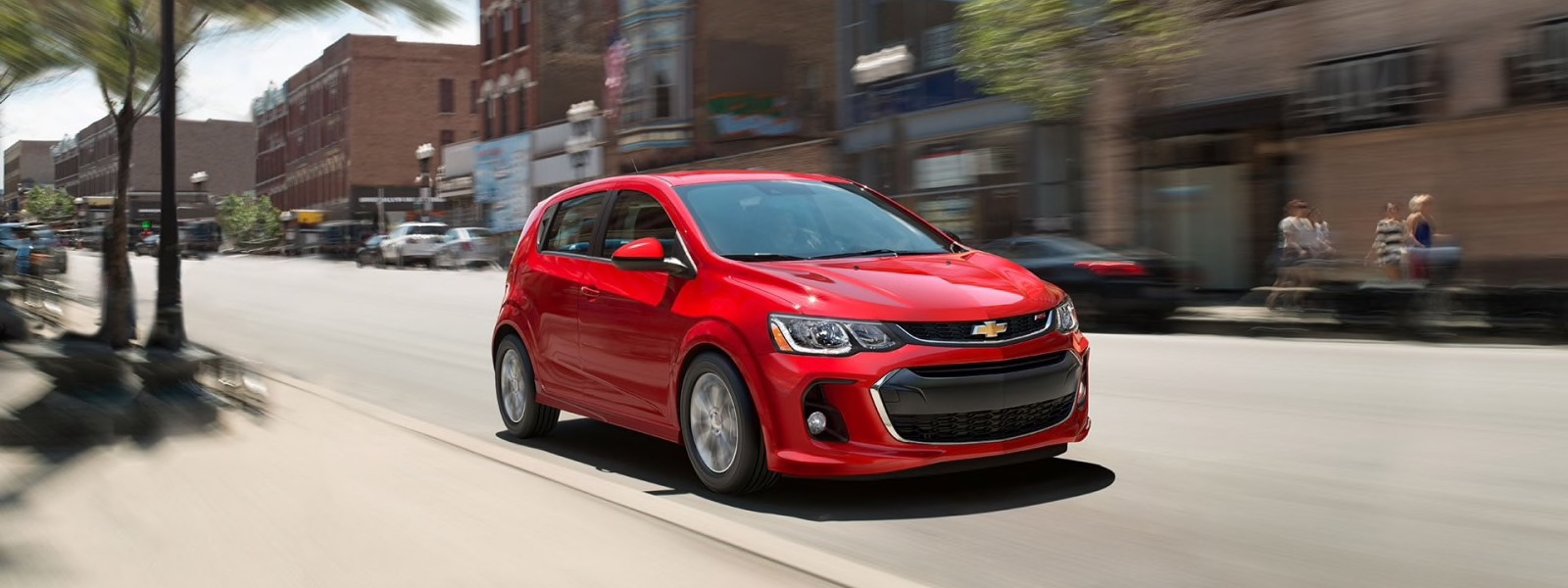 A red 2017 Chevy Sonic is driving on a street in Albany, NY.