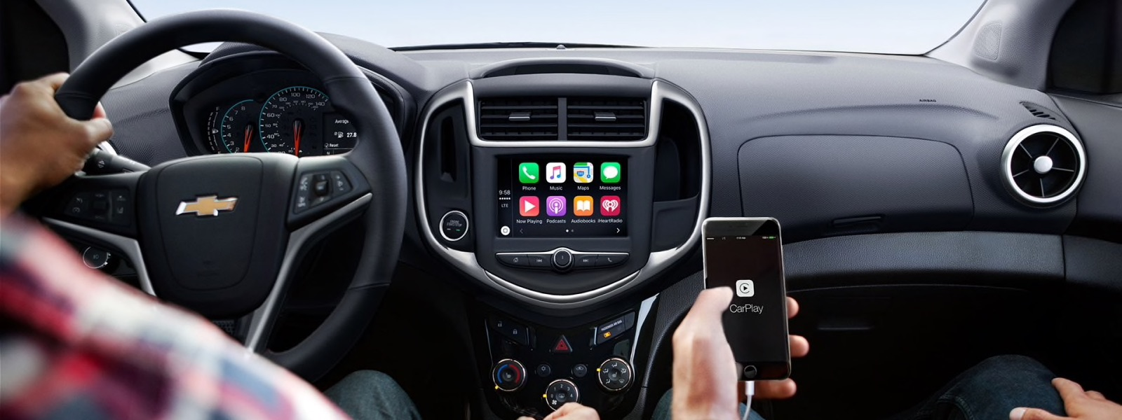 Passengers inside a 2017 Chevy Sonic are using a phone to connect to the infotainment system.