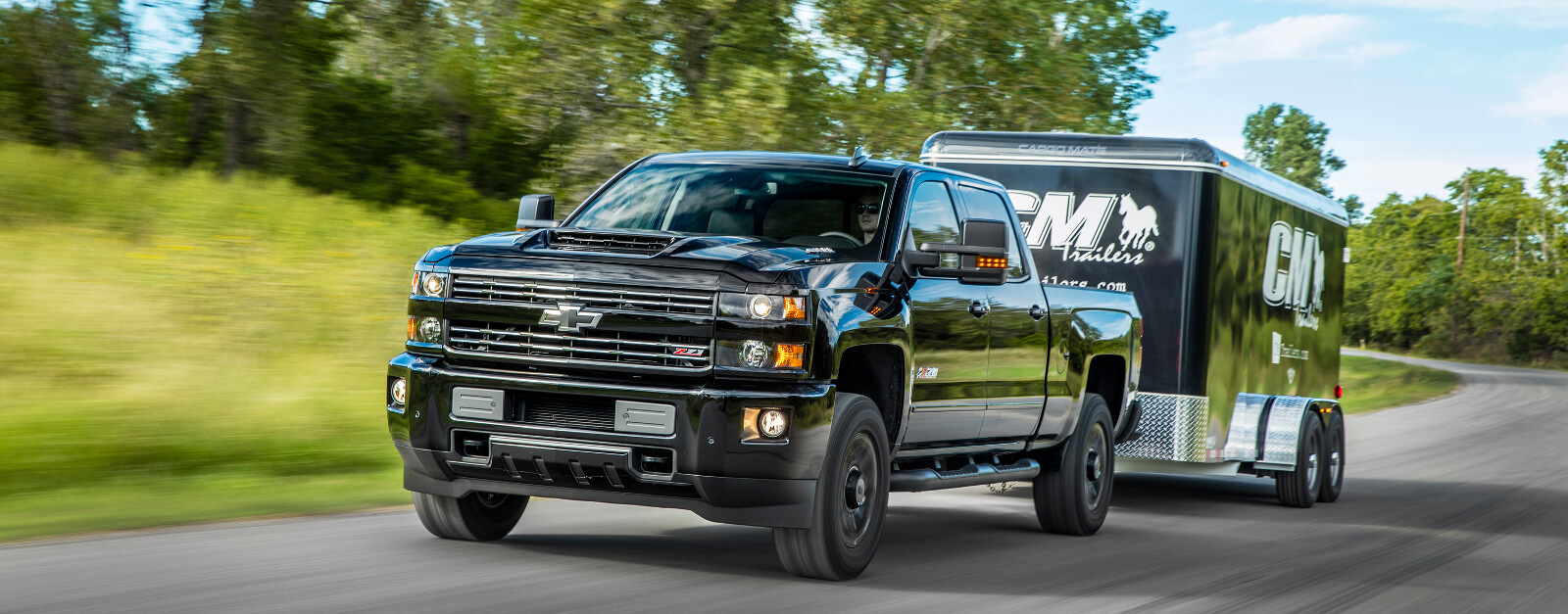 A black 2017 Chevy Silverado 1500 LTZ is driving on a road near Albany and towing an enclosed trailer.