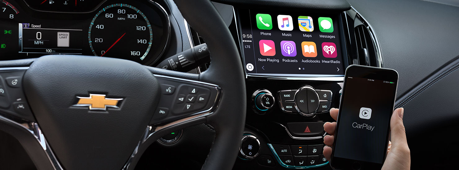 A hand is holding a phone inside a 2017 Chevy Cruze to connect to the infotainment system.