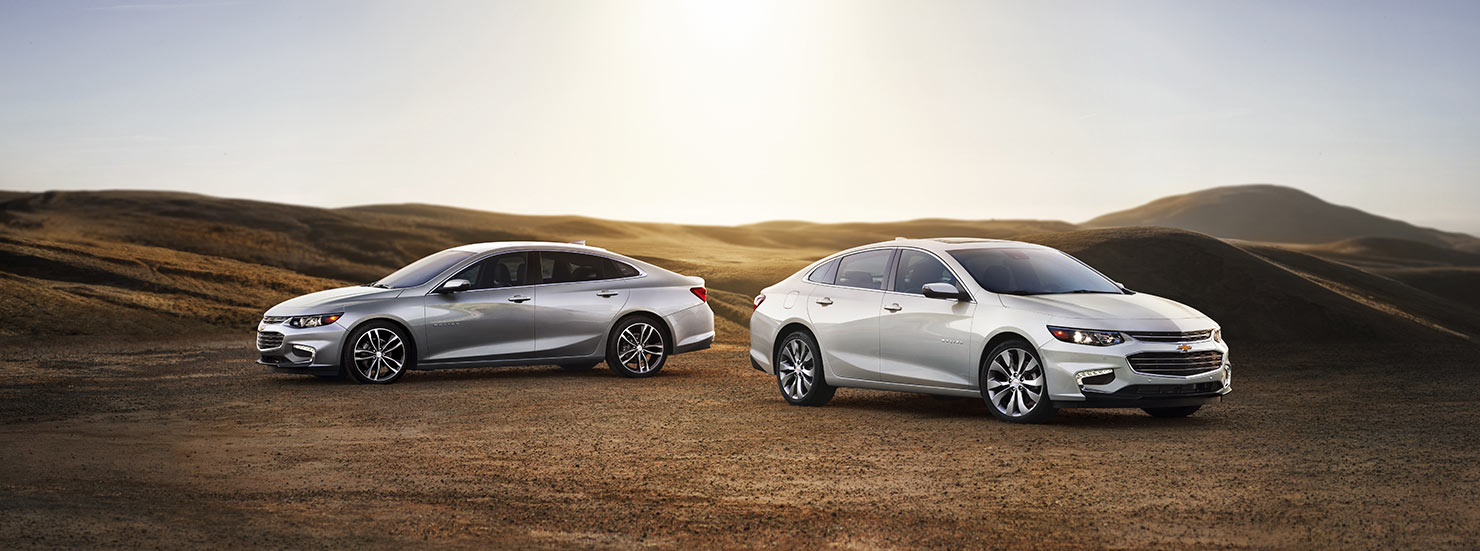Two silver 2017 Chevy Malibu sedans are parked in a field.