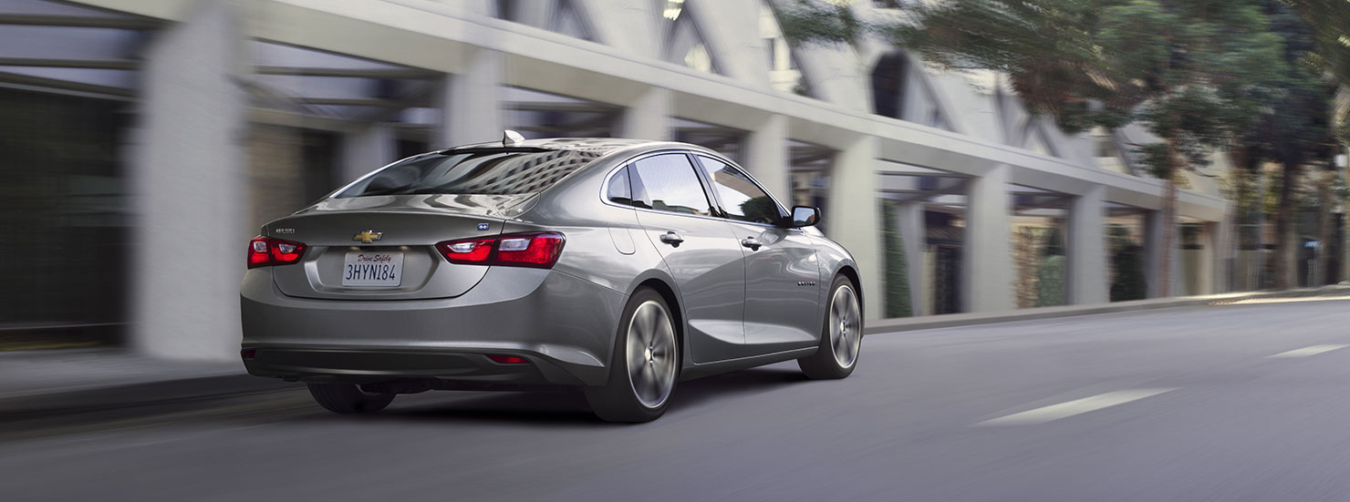A gray 2017 Chevy Malibu is driving on a street in Albany, NY.
