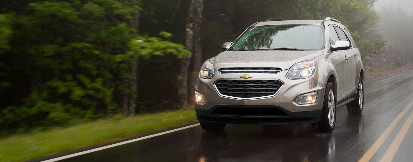 A beige 2017 Chevy Equinox is driving on a rural highway in the rain near Albany, NY.