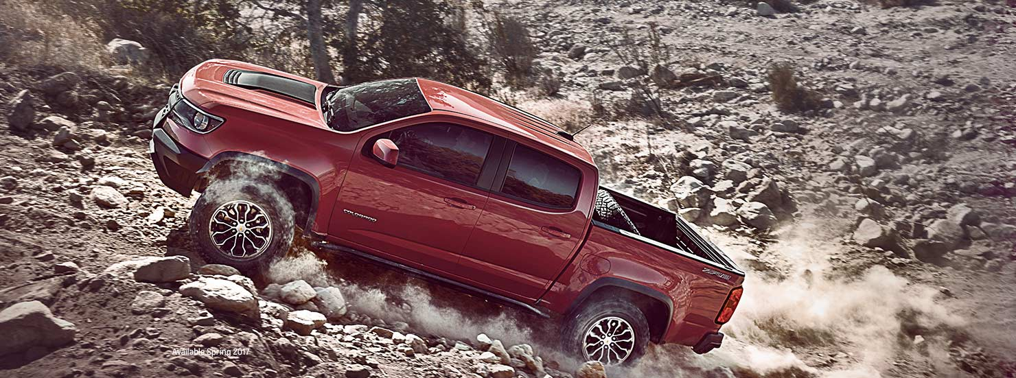 A red 2017 Chevy Colorado is off-roading on a dirt trail outside of Albany, NY.