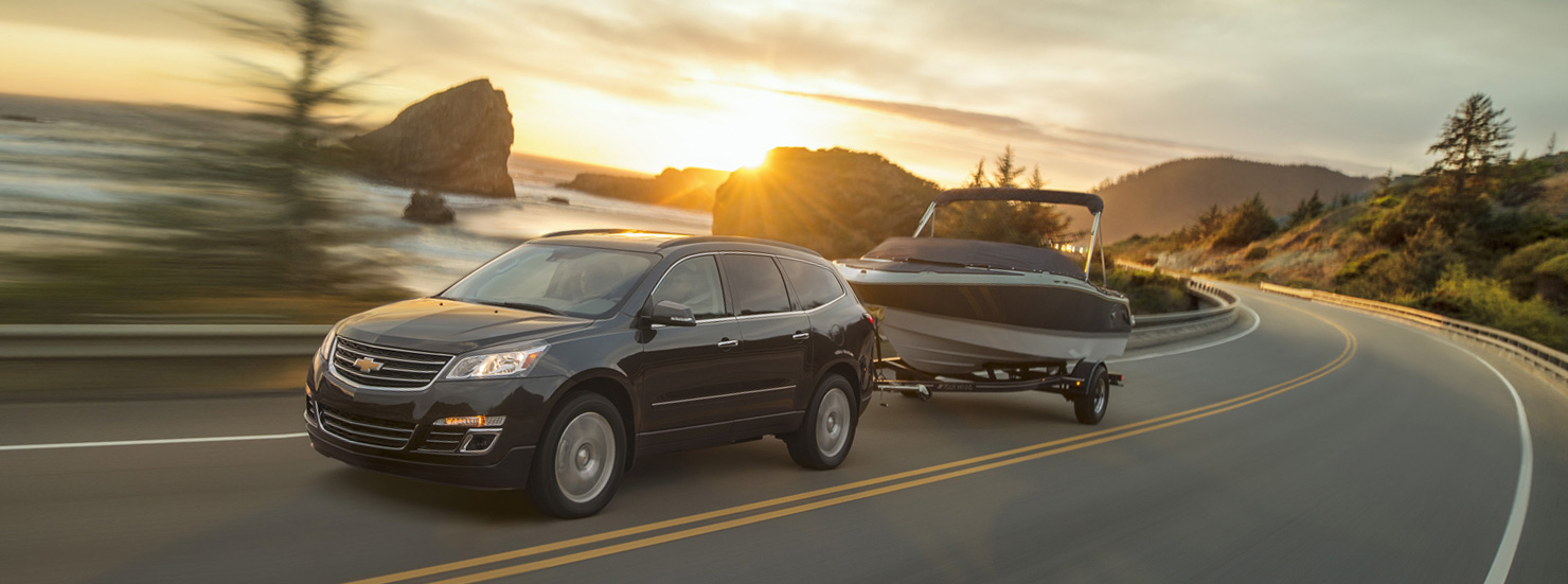 A black 2017 Chevy Traverse is towing a boat along the coast at sunset.