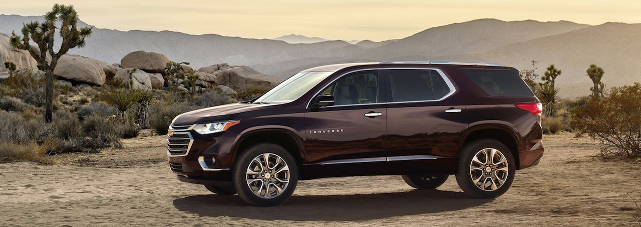 A purple 2018 Chevy Traverse is parked in a desert at dusk.