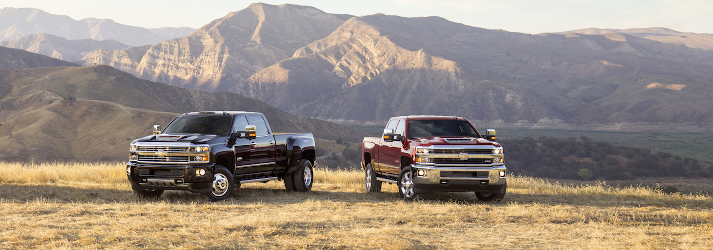 A black 2017 Chevy Silverado 3500HD and a red 2500HD are parked in a field in front of mountains.