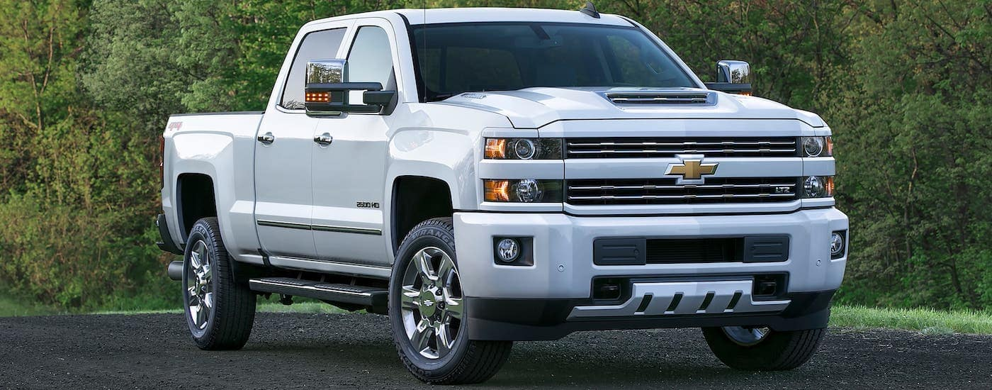 A white 2017 Chevy Silverado 2500HD LTZ is parked in front of trees in Albany, NY.