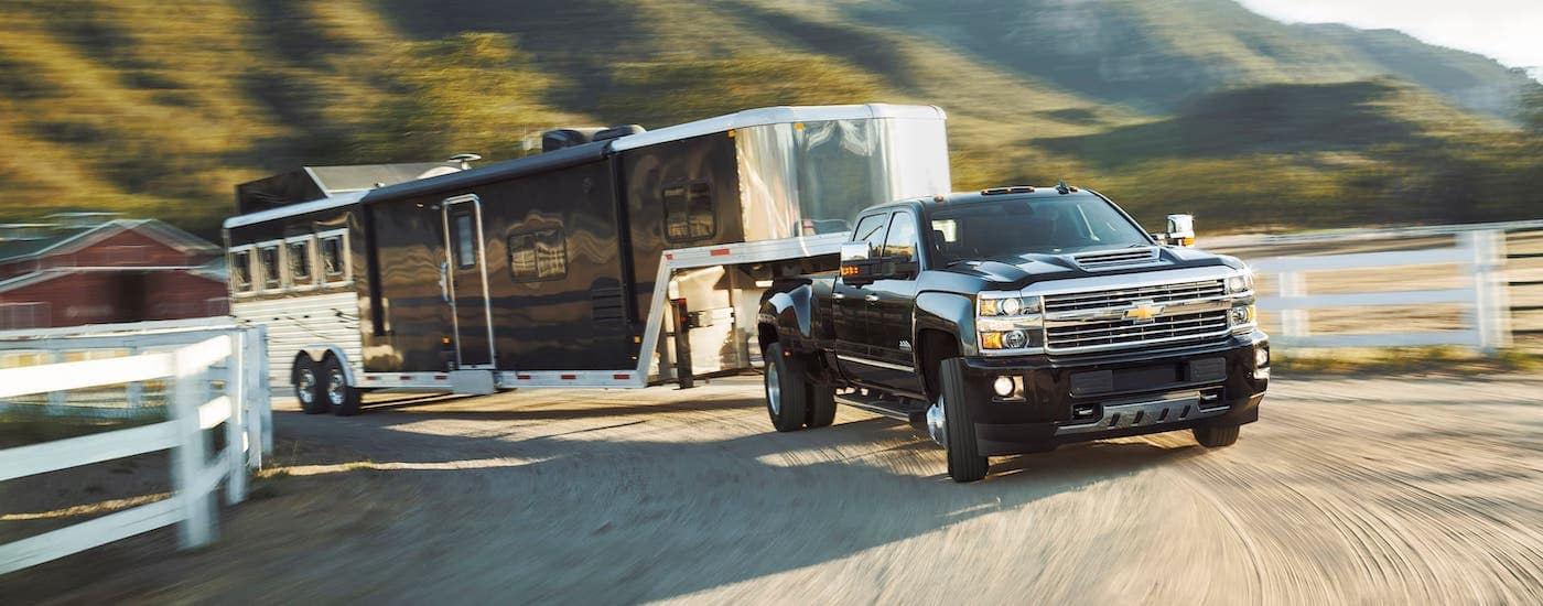 A black 2017 Chevy Silverado 3500HD is towing a large enclosed trailer on a ranch.