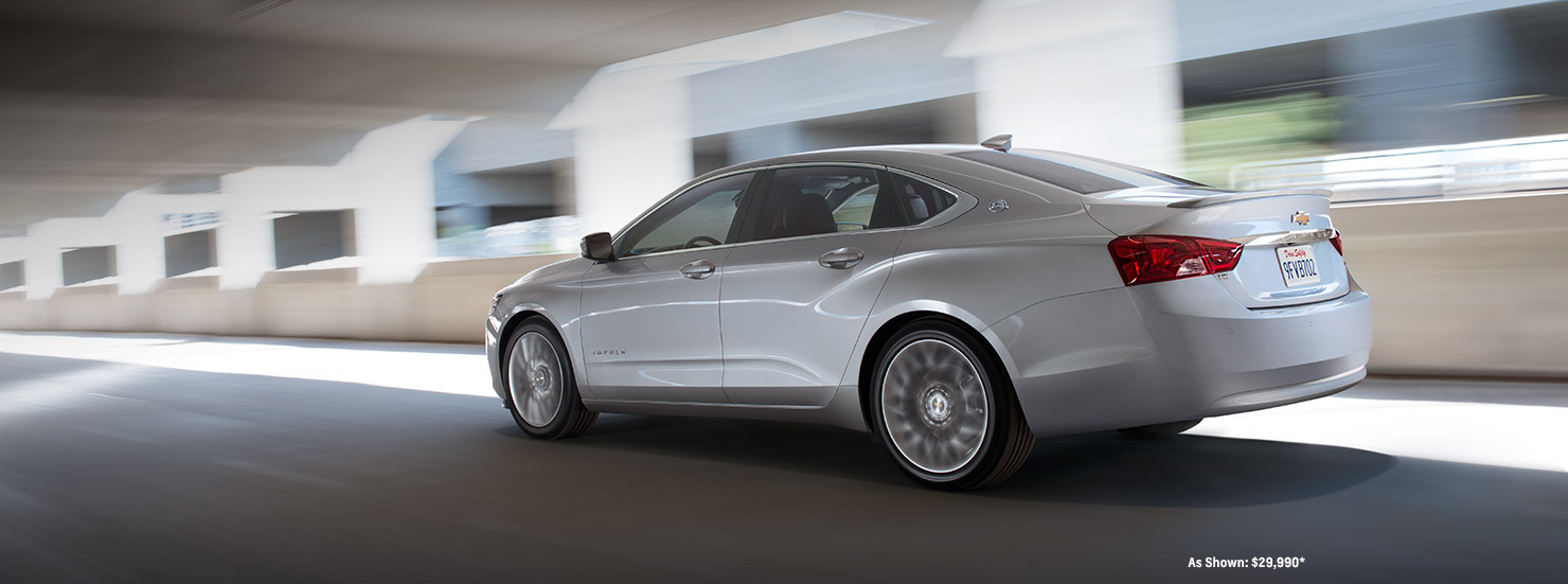 A silver 2017 Chevy Impala is driving under a bridge in Albany, NY.