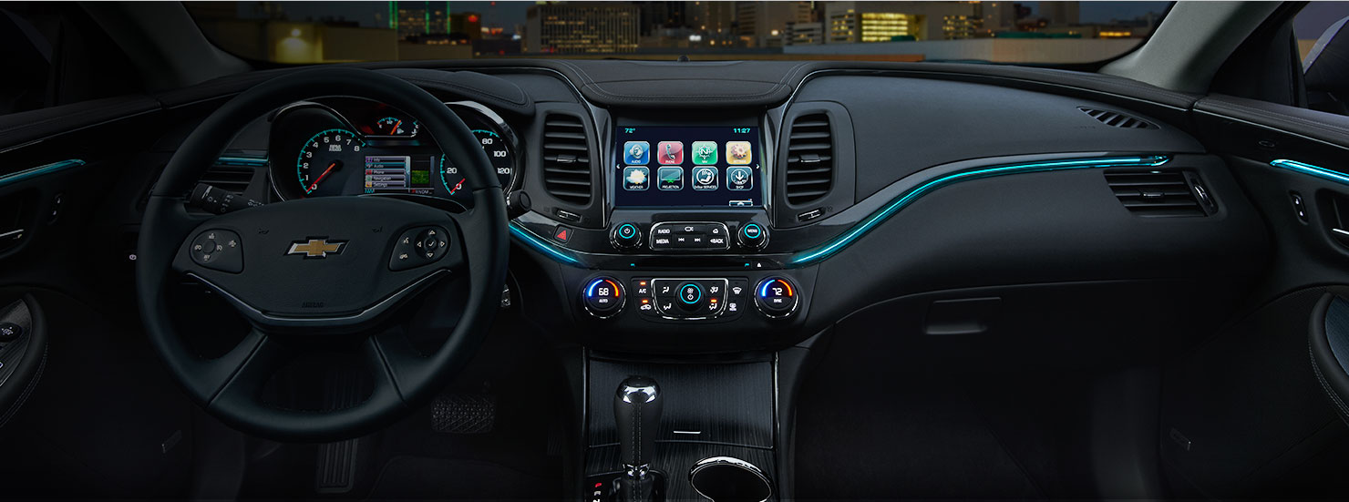 The black interior dashboard is shown of a 2017 Chevy Impala at night.