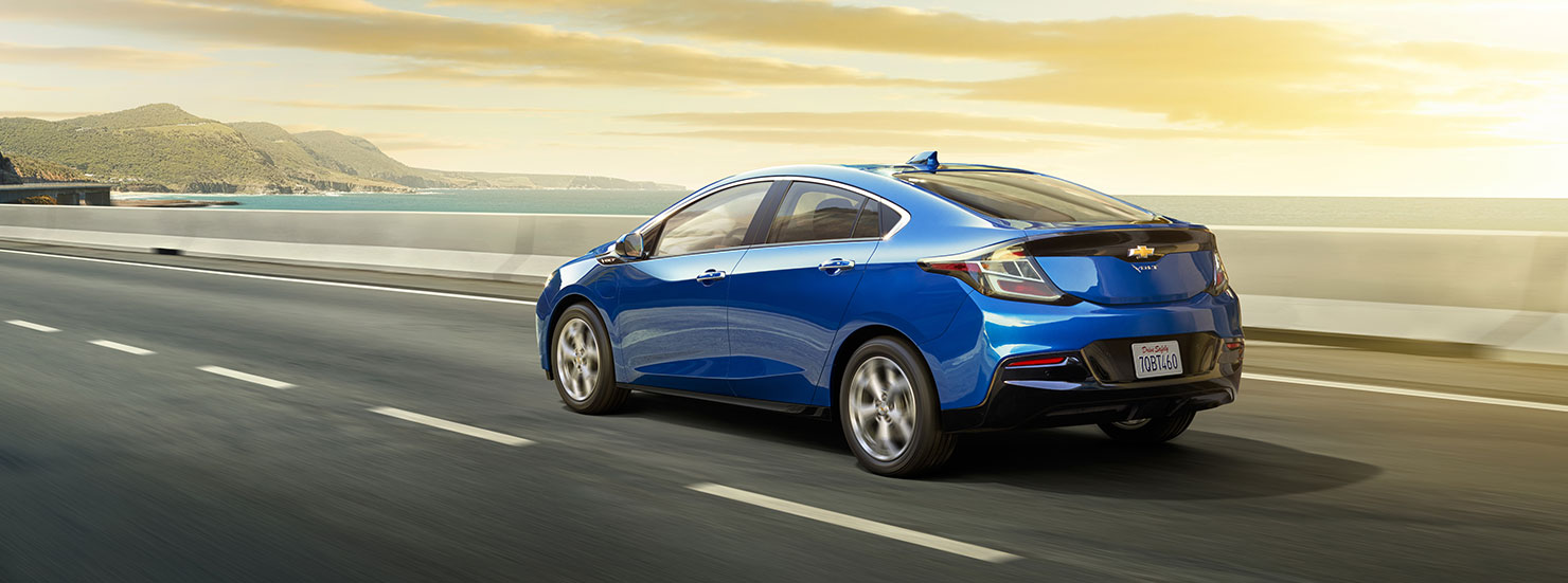 A blue 2017 Chevy Volt is driving along the coast at sunset.