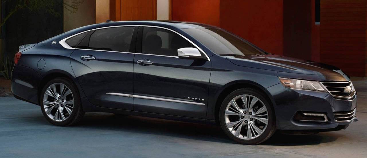 A black 2017 Chevy Impala is parked in an Albany driveway.