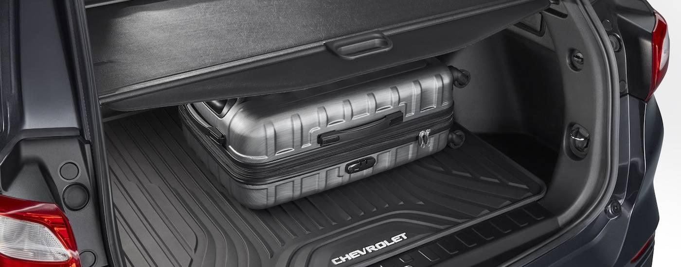 Luggage is shown in the cargo area of a gray 2018 Chevy Equinox.
