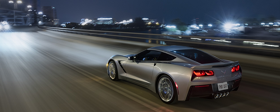 Silver 2019 Chevy Corvette Stingray driving down a highway at night with a city in the background