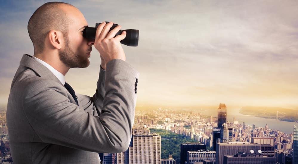Man looking through binoculars at a city scene