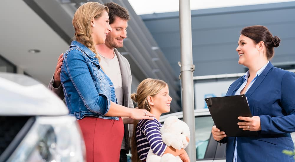 Husband, wife, and daughter working with a saleswoman purchasing a new vehicle