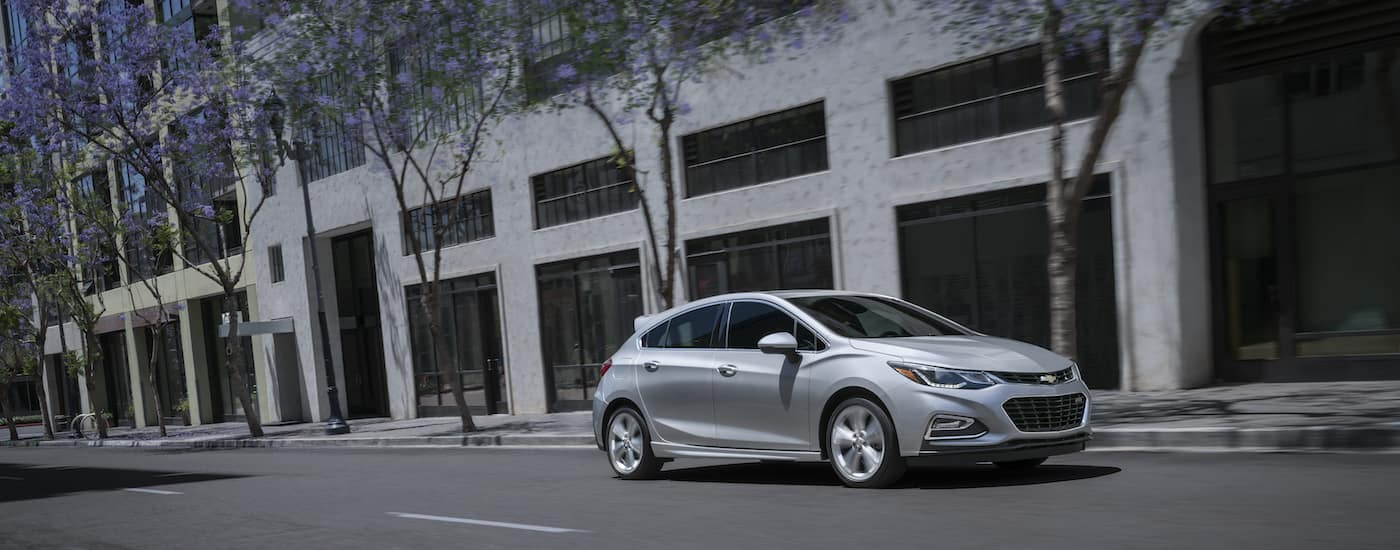 A silver 2018 Chevy Cruze is driving on a street in Albany, NY.