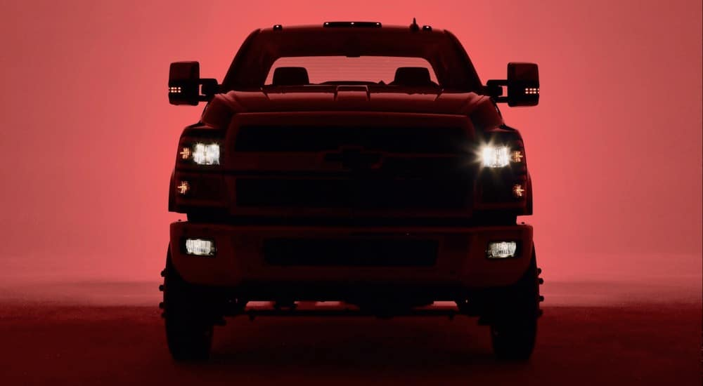 Chevy truck hidden by a dark shadow with red lighting behind it