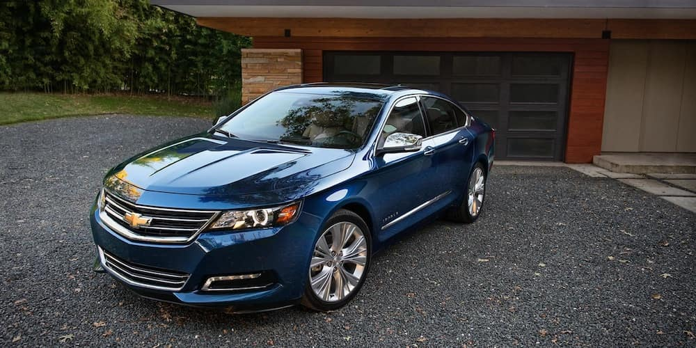 Blue 2018 Chevrolet Impala parked in front of a house