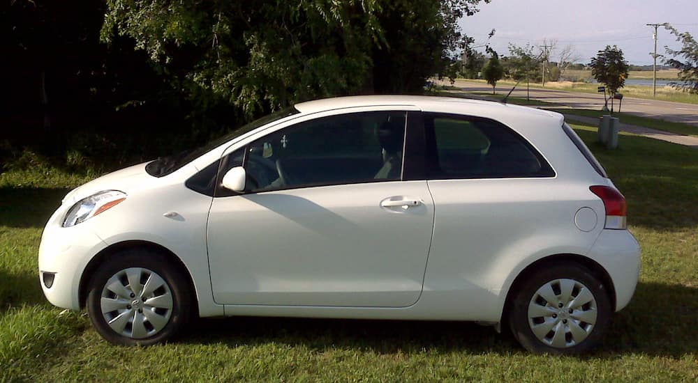White 2010 Toyota Yaris on lawn near road and water