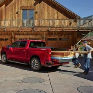 man and woman filling a red 2019 silverado 1500 rst with lumber