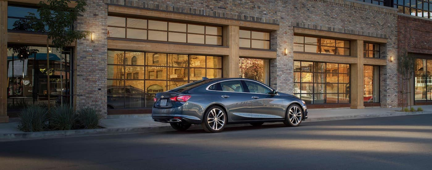 A dark grey 2020 Chevy Malibu, a popular car at Chevy dealerships near Clifton Park, NY, is parked in front of a brick building at night.