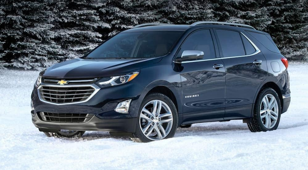 A blue 2020 Chevy Equinox is parked in snow next to pine trees near Clifton Park, NY.