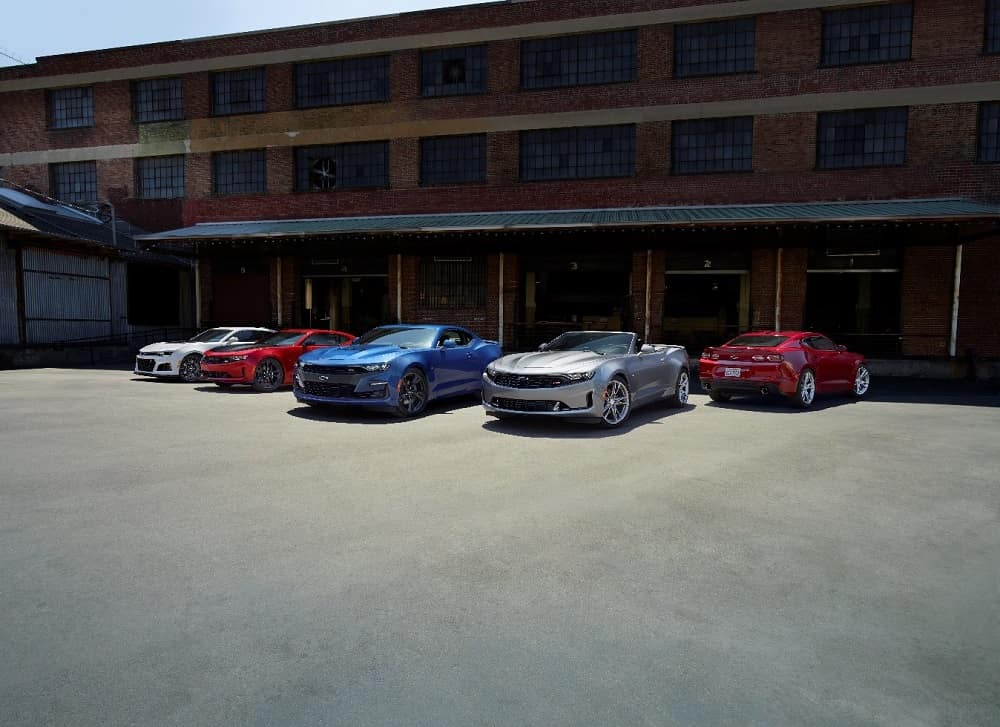 Five 2019 Chevrolet Camaros automobiles parked in front of an industrial building on a sunny day in different shades of white, red, blue and silver