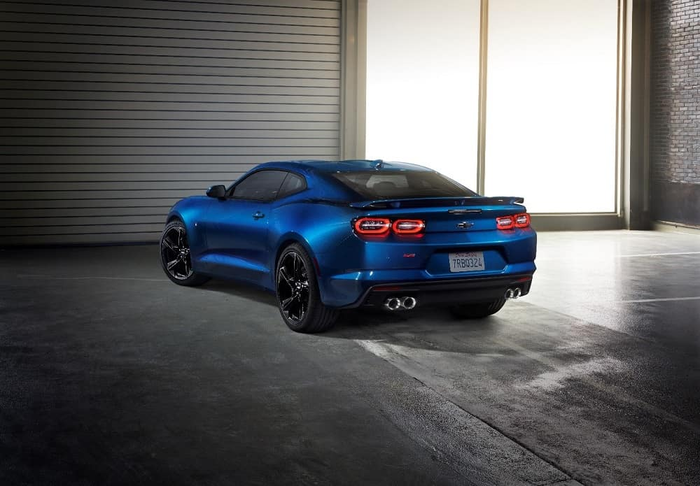 Rear shot of a blue 2019 Chevrolet Camaro 2SS sportscar parked in a garage with large windows
