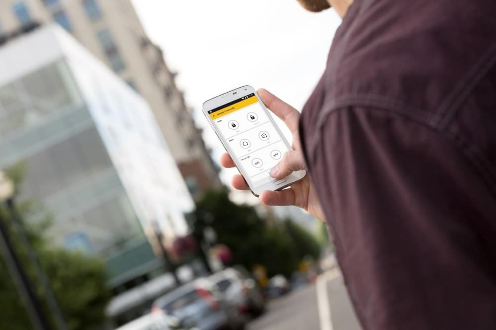 Man holding a white Android cellphone with myChevrolet app on the screen looking for his Chevy vehicle in a city