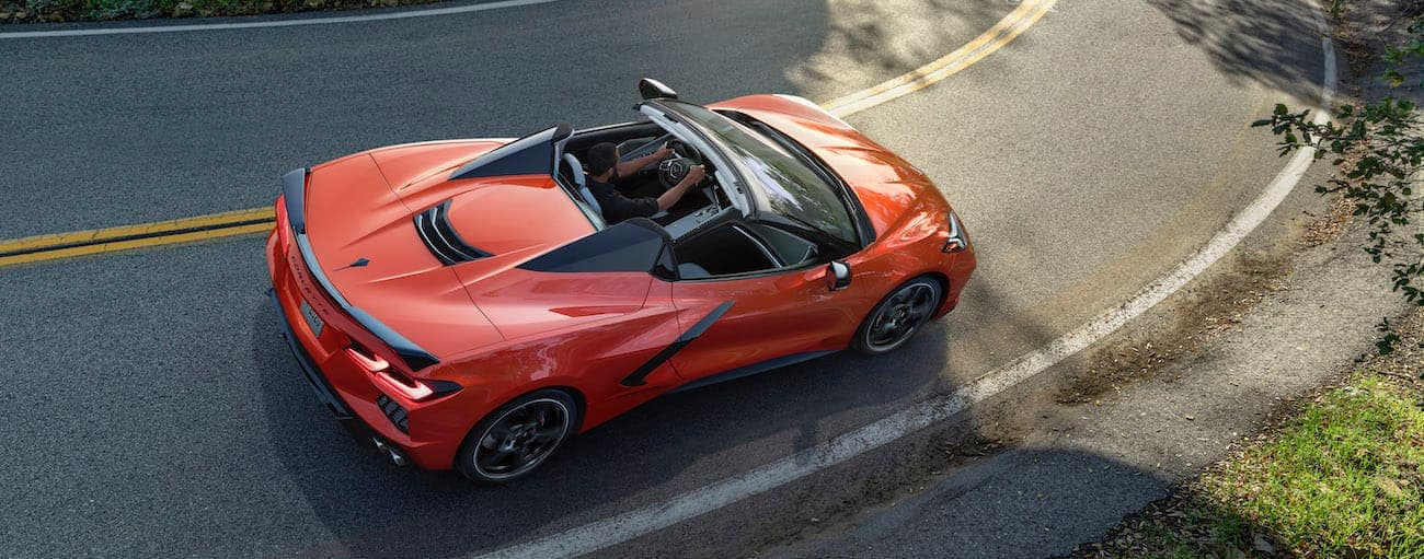 An orange convertible 2020 Chevy Corvette is shown from above on a road in Albany, NY.