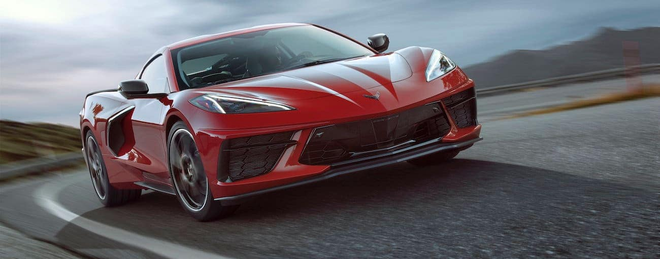 A red 2020 Chevy Corvette is driving on an overcast day.