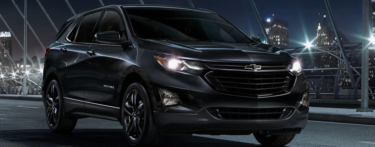 A black 2020 Chevy Equinox is on a bridge with a night time city skyline in the background.
