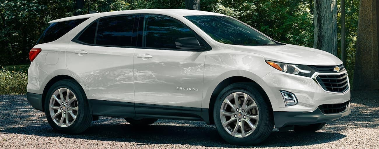 A white 2020 Chevy Equinox is parked on a tree-lined dirt road near Albany, NY.