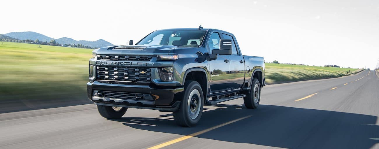 A black 2020 Chevy Silverado HD 2500 is driving on a highway near Albany, NY.