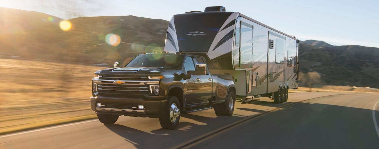 A black 2020 Chevy Silverado HD 3500 is towing a large camper.