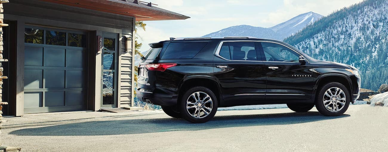 A black 2020 Chevy Traverse is parked outside a home near Albany, NY, with mountain views.