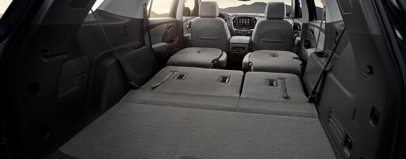 The seats are folded down to show the cargo room in the grey interior of a 2020 Chevy Traverse.