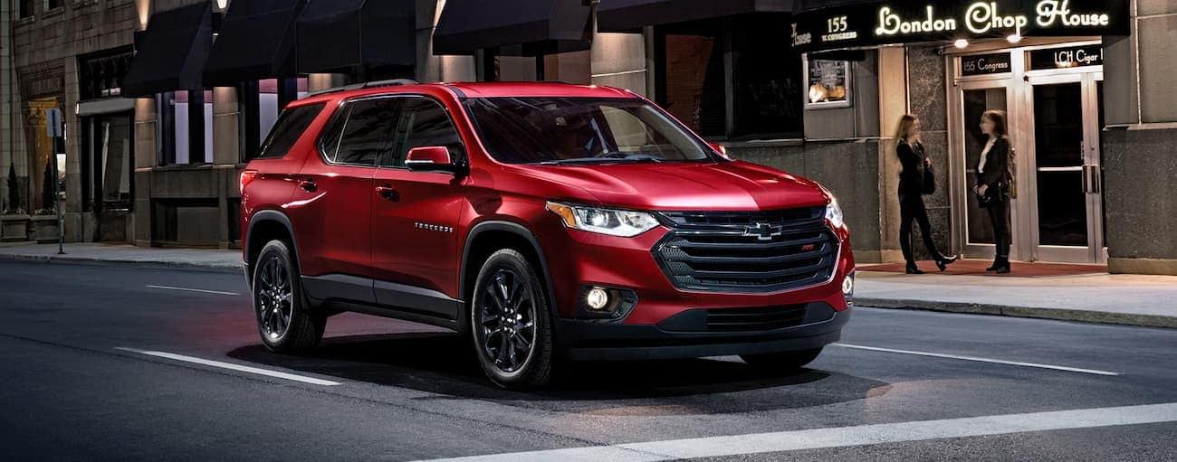 A red 2020 Chevy Traverse RS is stopped at a city intersection at night near Albany, NY.